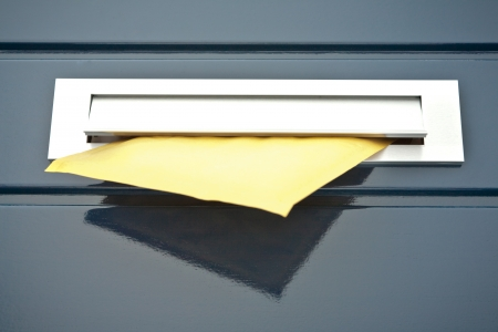 Closeup image of a front door built-in mailbox with a yellow parcel or letter partially in it.