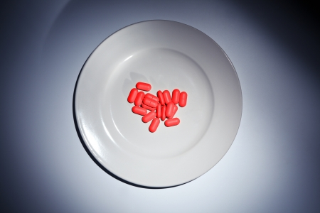 Many red pills on a white plate under dramatic light. Stock Photo - 20224307