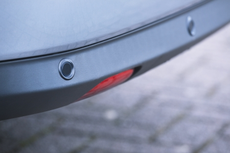 reverse: Closeup image of rear bumper parking sensors, also known as reverse park assist