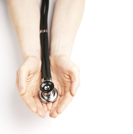Female hands holding a stethoscope over a plain white background  A concept of caring for health or offering medical help  photo