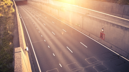 An empty highway or motorway emerging from a tunnel, photographed at sunset.