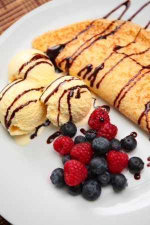 A delicious pancake with fresh fruits (raspberries and blueberries), vanilla ice cream and chocolate sauce, served in a white plate. photo