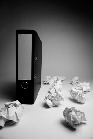 A concept image of disorder in office organization, archives or files. Many crumpled papers around a black folder with dramatic lighting. Stock Photo - 20259732