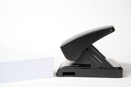 paper puncher: An office paper puncher on plain background next to a stack of white paper, with copy space, photographed in profile (from the side).