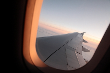 utilized: Photograph of a sunsetsunrise view through an airplane window. The free space in the sky could be utilized as copy space. Stock Photo
