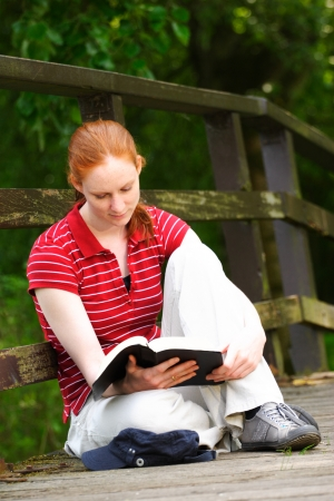bible reading: A casual young woman reading her Bible outdoors.