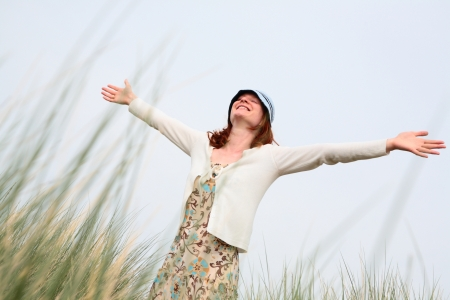 A beautiful young woman experiencing freedom or good time among dunes grass with her arms stretched far out and eyes closed. Could also be used as a concept image for worship, joy, etc.