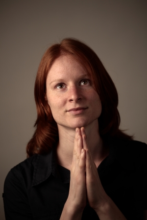 A young woman praying to God with open eyes in dramatic lighting and on plain dark background. Stock Photo