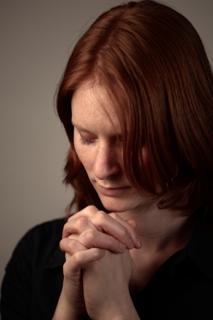 A young woman praying to God with closed eyes in dramatic lighting and on plain dark background
