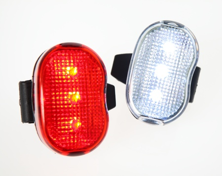 Two bicycle lights on plain background.