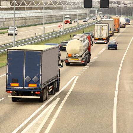 Een drukke snelweg vol met auto's en vrachtwagens. Vierkante samenstelling. Stockfoto - 20260432