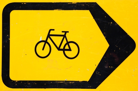 diversion: A bright yellow and black road sign notifying of a bicycle lane diversion due to road works.