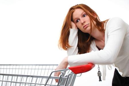 Een triest winkelen meisje leunend op haar lege winkelwagen. Stockfoto - 20362150