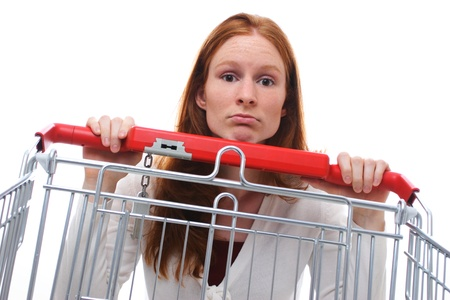 pitiful: A sad shopping girl hanging behind her empty shopping cart. Stock Photo