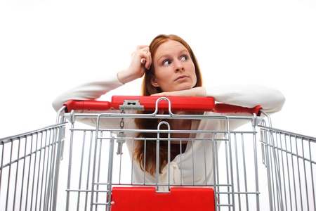 A young Caucasian housewife choosing her shopping products while leaning on her empty shopping cart. photo