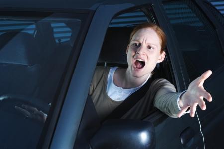 Egy dühös fiatal női vezető a kocsiját, kezükben az ablakon, és üti a kürt