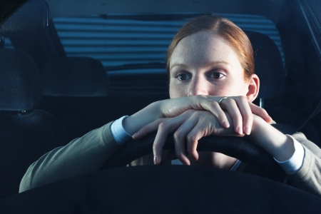 A young female driver being bored behind the steering wheel in her car. This is a nighttime scene. photo