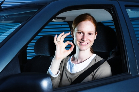 perfect sign: A young female driver making an OK or perfect gesture from the inside of a car. This image could represent a person graduating from or taking driving lessons. Stock Photo