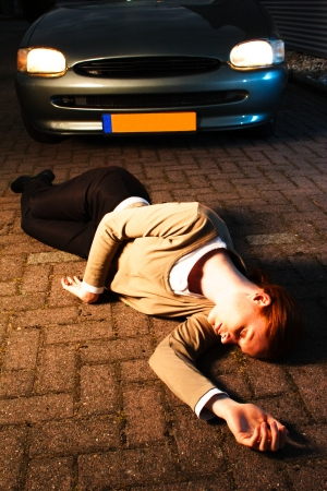 mishap: A dead or injured woman laying on the ground after she has been hit by a car in an accident at night