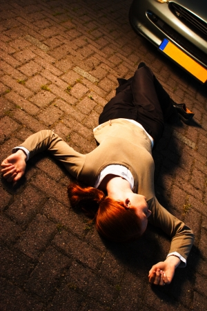 misadventure: A woman laying on the ground after she has been hit by a car in an accident at night  Stock Photo