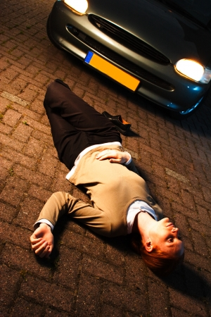 car crime: Scene with a dead or injured woman laying on the ground after she has been hit by a car in an accident at night  Stock Photo