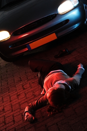 Injured woman laying on the ground after she has been hit by a car in an accident at night  Stock Photo