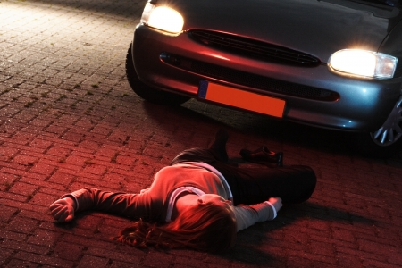 mishap: A supposedly dead or injured woman laying on the ground after she has been hit by a car in an accident at night  Stock Photo