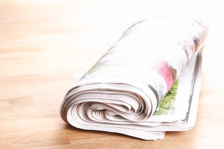 Folded daily newspaper on wooden background. Stock Photo - 20358734