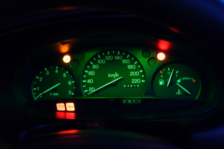 warning lights: A closeup on the dashboard of a car with warning lights on at night.