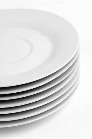 A stack of kitchen dishes, dessert plates on plain background. Stock Photo