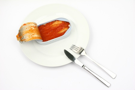 Canned herring on a plate with utensils over a white background.