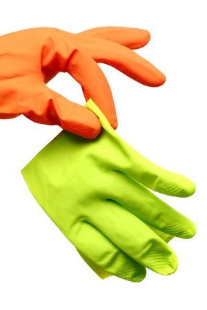Hand in an orange cleaning glove holding a green glove as if it were disgustingly dirty - isolated on white background. Stock Photo - 20381360