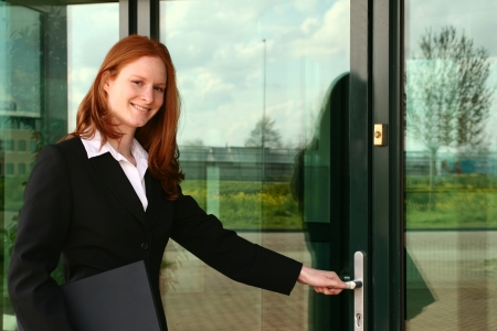A confident young Caucasian businesswoman with a laptop in front of the entrance of a corporate building. Stock Photo