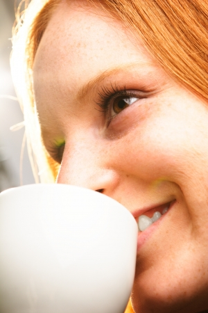 A happy young woman with white coffee or tea cup in her hands smiling. photo