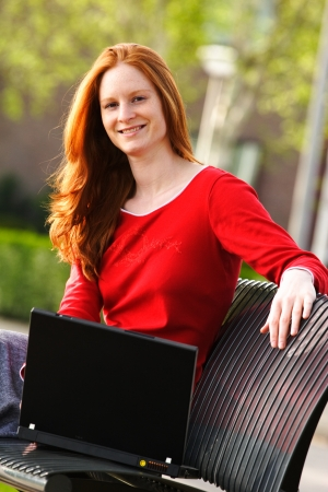 A smiling young Caucasian female student working on a laptop outdoors. photo