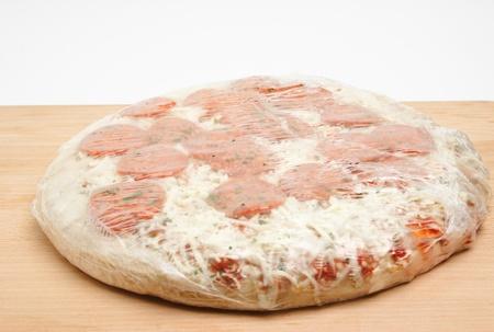 木製のまな板の上の深い冷凍ピーマンのピザ。