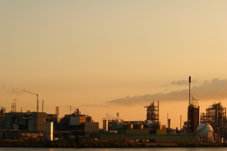 A riverside factory at sunset with an almost clear sky. photo