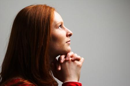 Een jonge vrouw bidden tot God in dramatische verlichting en op effen achtergrond. Stockfoto