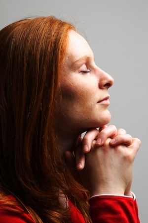 A young woman praying to God with closed eyes in dramatic lighting and on plain background.