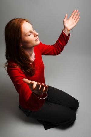 A young woman worshiping God - praying and praising. Stock Photo