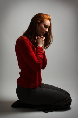 donna in ginocchio: Una giovane donna in preghiera a Dio con illuminazione drammatica e su sfondo chiaro. Archivio Fotografico