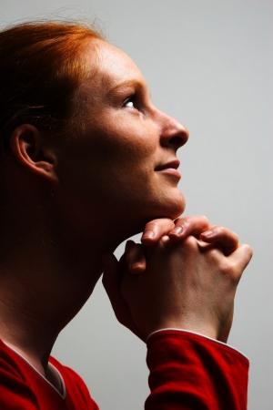 Egy fiatal nő hálát adva Istennek egy imádkozó helyzetben örömteli kifejezést, és nyitott szemmel. Stock fotó