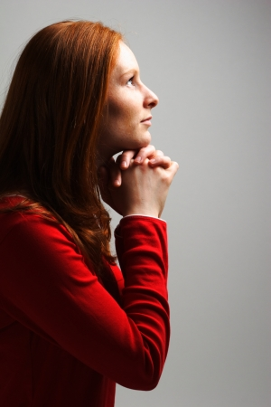 intercession: A young woman praying to God in dramatic lighting and on plain background with copy space on the right.