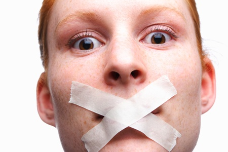 speechless: Face of a young woman with tape on her mouth - a concept of censored speech.