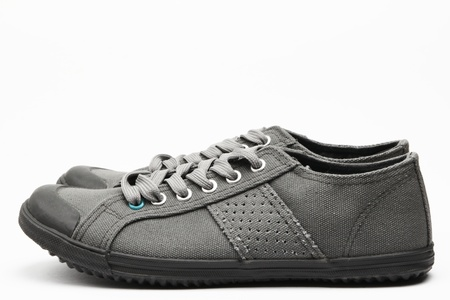 informal clothes: A pair of gray casual female shoes on plain background.
