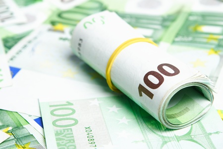 eur: A roll of 100 Euro bills laying over spread banknotes of the same value. Stock Photo