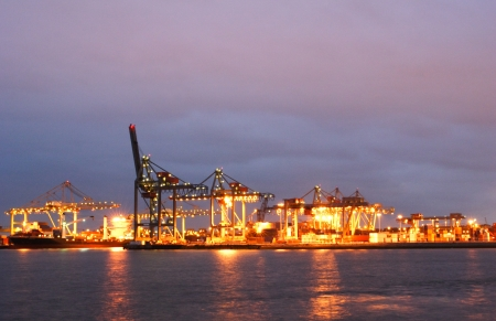 The cranes and docks at the Rotterdam seaport on a cloudy night. Stock Photo