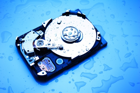 An uncovered computer hard disk device with water drops on and around it, lit in blue. photo