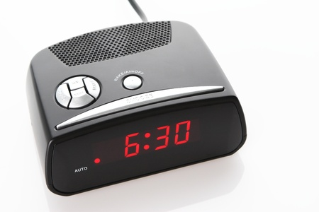 A digital alarm clock showing 6:30am over white background with a natural reflection under it. photo