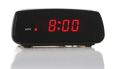 A digital alarm clock showing 8:00am over white background with a natural reflection under it. Zdjęcie Seryjne